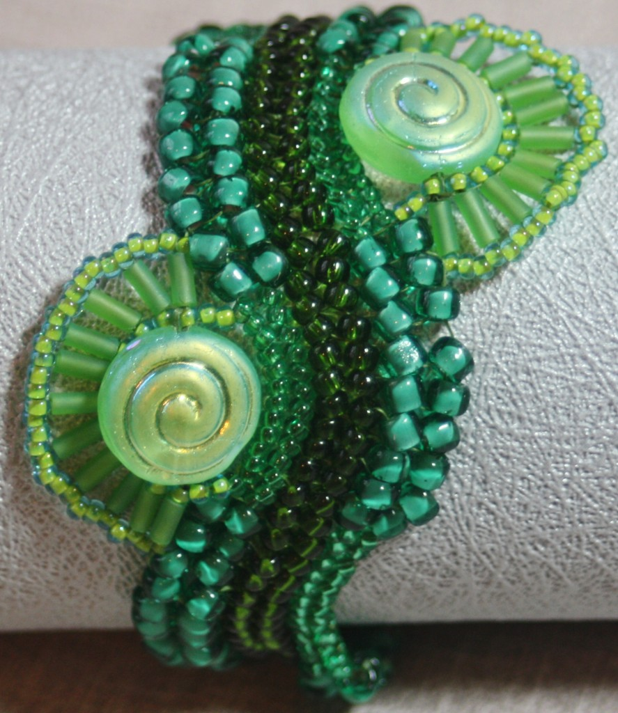 photo of Green River Bracelet using different sized green seed beads in a wavy herringbone stitch and two round disc beads with waves of green bugle beads on either side of the bracelet by Amanda Crago of Bowerbird Jewellery